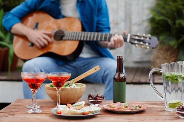 Photo recadrée d'un homme méconnaissable jouant de la guitare lors d'une fête sur le toit avec des verres à cocktail au premier plan, espace pour copie