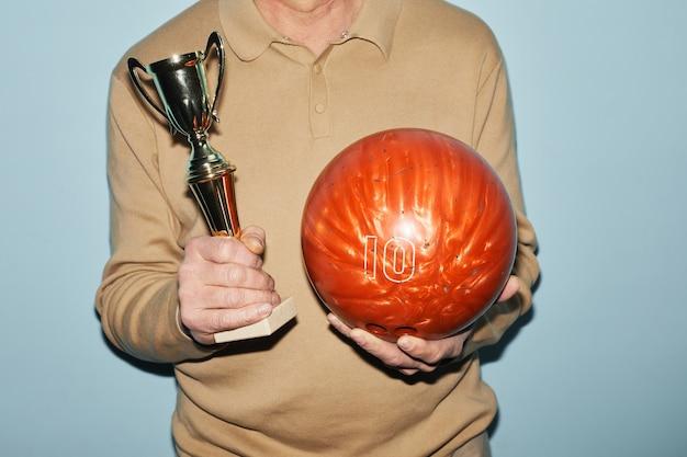 Photo recadrée d'un homme mûr méconnaissable tenant un trophée et une boule de bowling en se tenant debout sur fond bleu, espace pour copie