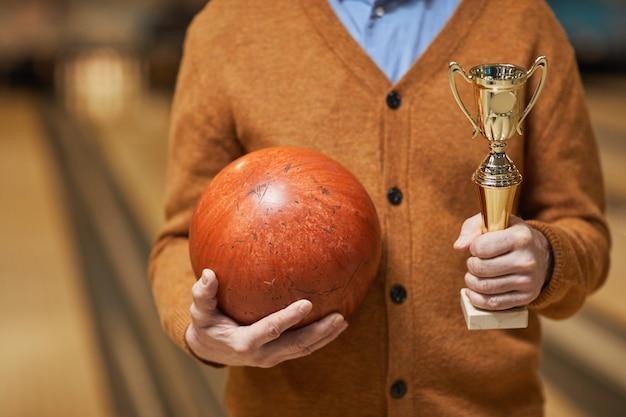 Photo recadrée d'un homme mûr méconnaissable tenant un trophée et une boule de bowling tout en posant au bowling après avoir remporté le match, espace de copie