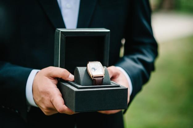 Photo recadrée d'un homme portant un costume élégant et tenant une montre-bracelet. main d'homme avec une montre de luxe élégante et chère avec un bracelet en cuir sur un fond de nature.