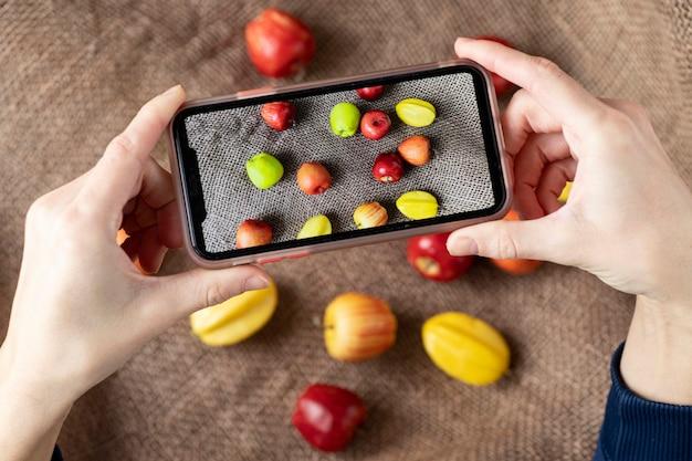 Photo recadrée de l'homme tenant le meilleur smartphone tenant la photo de fruits