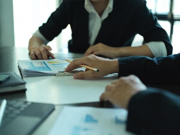 Photo recadrée d'hommes d'affaires analysant le graphique de l'entreprise dans la salle de réunion