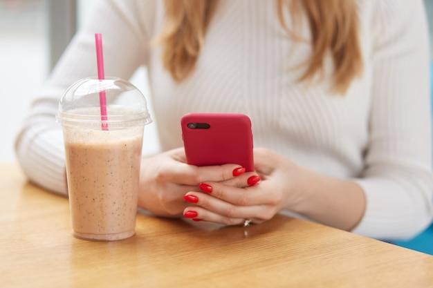 Photo recadrée intérieure d'une femme méconnaissable tenant son smartphone dans les deux mains