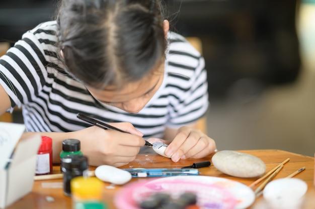 Photo recadrée de la jeune artiste peignant à la couleur de l'eau sur un rocher