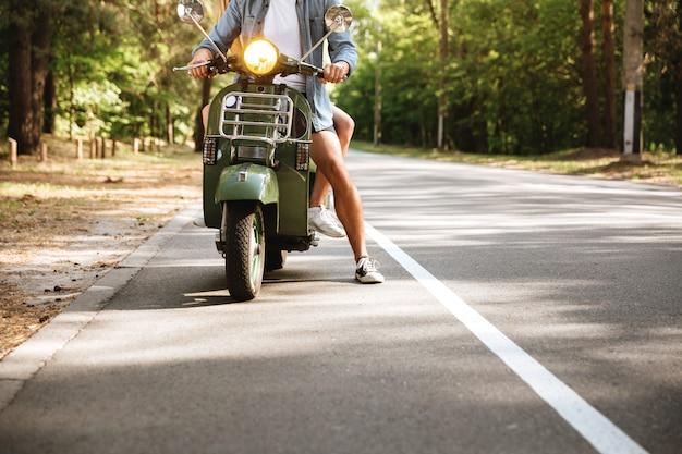 Photo recadrée de jeune couple d'amoureux attrayant sur scooter