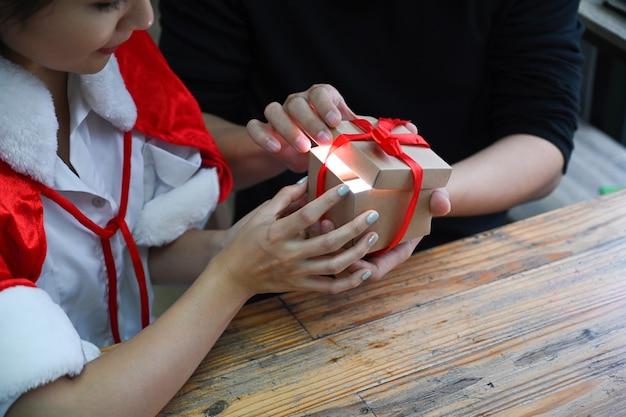 Photo recadrée jeune couple ouvrant ensemble une boîte-cadeau de noël.