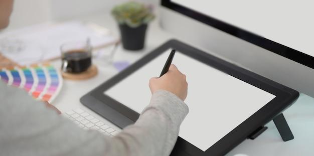 Photo recadrée de la jeune designer féminine révisant son projet avec tablette numérique