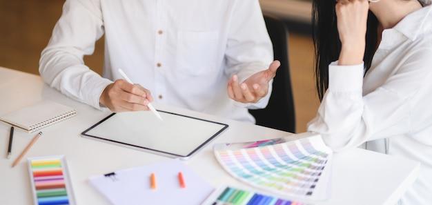 Photo recadrée d'une jeune équipe de designers professionnels travaillant sur son projet tout en utilisant une tablette numérique