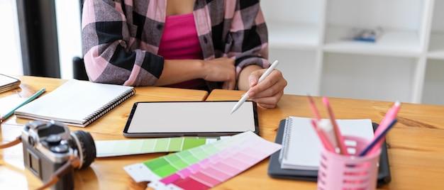 Photo recadrée d'une jeune étudiante designer faisant une affectation sur une tablette numérique