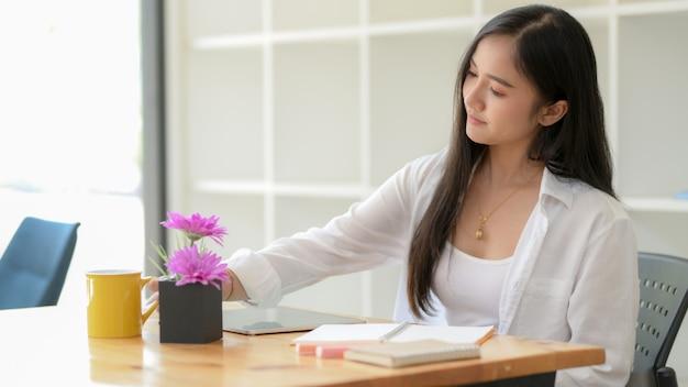 Photo recadrée d'une jeune étudiante à l'université prendre une courte pause et boire un café