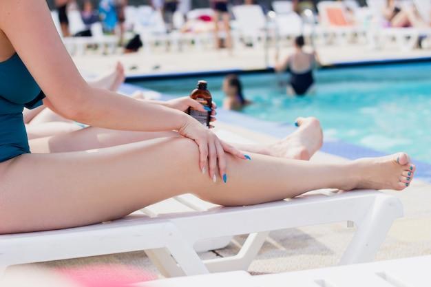 Une photo recadrée d'une jeune femme appliquant un écran solaire sur ses jambes