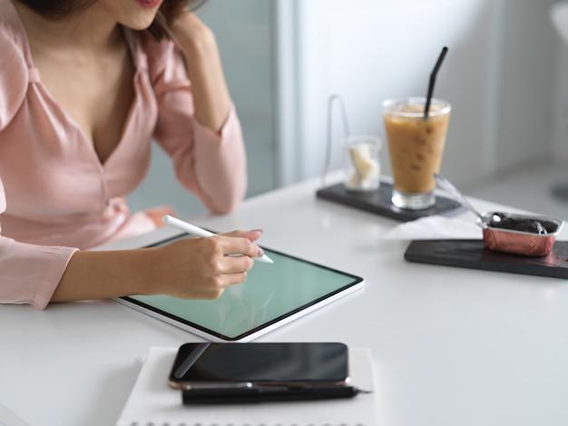 Photo recadrée de jeune femme écrivant sur une maquette de tablette d'espace vide dans une chambre confortable