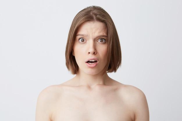 Photo recadrée d'une jeune femme embarrassée étonnée aux cheveux noirs