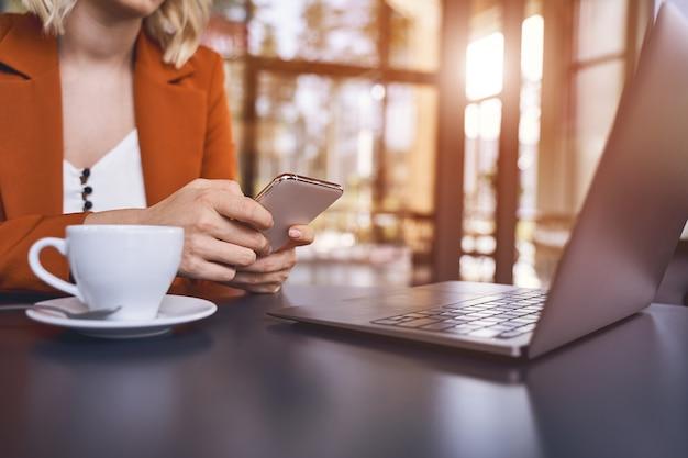 Photo recadrée d'une jeune femme entrepreneur blonde avec un téléphone portable assis à un bureau