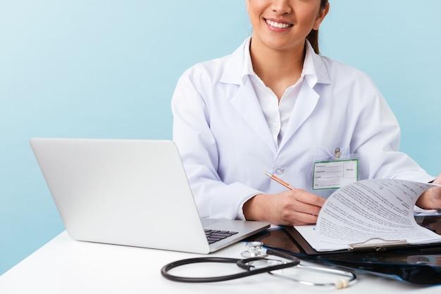 Photo recadrée d'une jeune femme médecin posant isolé sur un mur bleu à l'aide d'un ordinateur portable.