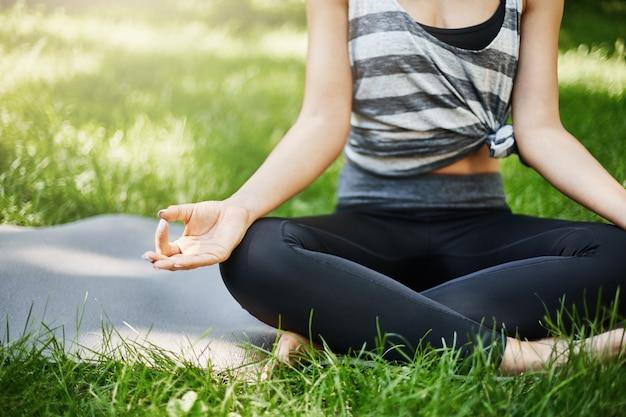 Photo recadrée d'une jeune femme méditant dans un parc public ou derrière sa maison à l'extérieur, loin de la technologie.