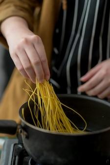 Photo recadrée de jeune femme préparant des ingrédients pour le menu de nouilles
