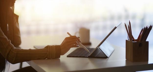 Photo recadrée de la jeune femme qui rédige son projet avec une tablette numérique dans un bureau moderne