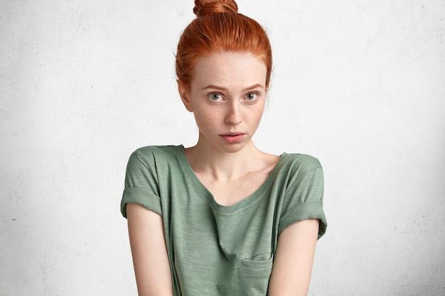 Photo recadrée d'une jeune femme rousse à la recherche agréable vêtue de vêtements décontractés, a déplu et surpris l'expression, isolée sur blanc