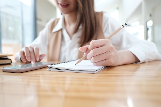 Photo recadrée d'une jeune femme utilisant un téléphone intelligent et préparant une note pour l'examen à la bibliothèque.