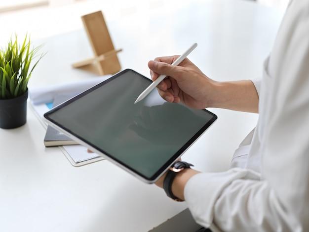 Photo recadrée de jeune homme d'affaires écrit sur une maquette de tablette dans une salle de bureau moderne