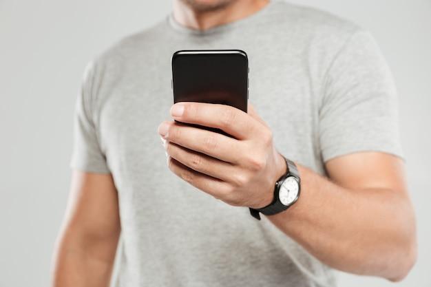 Photo recadrée de jeune homme à l'aide de la conversation par téléphone mobile.