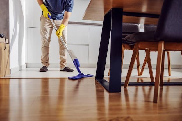 Photo recadrée d'un jeune homme bien rangé avec des gants en caoutchouc, nettoyer le sol de la cuisine avec une vadrouille.