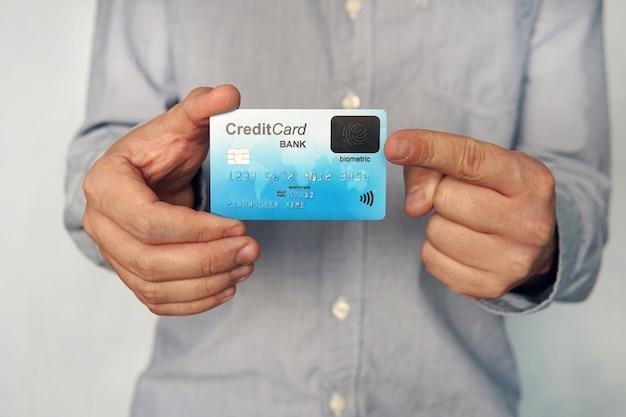 Photo recadrée d'un jeune homme en chemise montrant le recto de la carte de crédit avec un lecteur d'empreintes digitales dans son coin. concept d'utilisation de la biométrie dans le secteur bancaire. homme tenant une carte de paiement avec capteur biométrique. utilisateur.