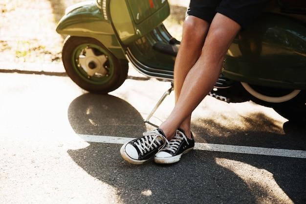 Photo recadrée de jeune homme debout près de scooter à l'extérieur.