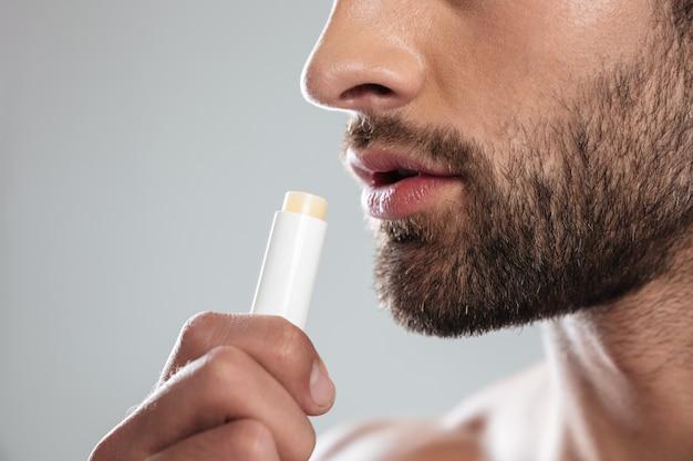 Photo recadrée de jeune homme avec du rouge à lèvres incolore