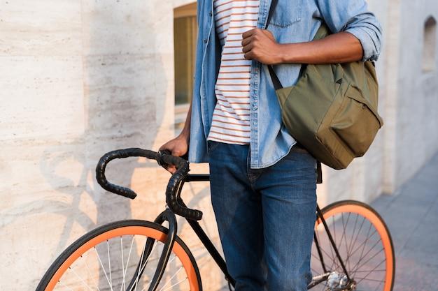 Photo recadrée d'un jeune homme marchant à vélo