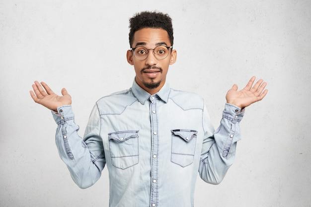 Photo recadrée de jeune homme à la mode porte des vêtements et des lunettes en denim, des gestes avec les mains,
