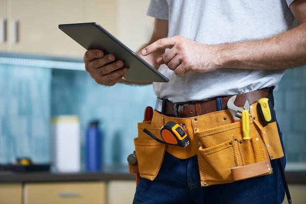 Photo recadrée d'un jeune réparateur portant une ceinture à outils avec divers outils à l'aide d'une tablette numérique tout en