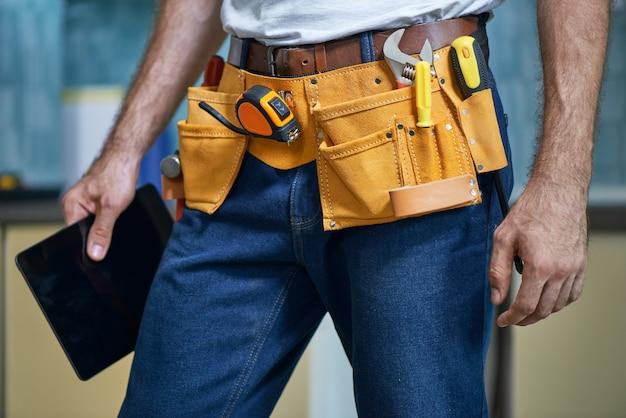 Photo recadrée d'un jeune réparateur portant une ceinture à outils avec divers outils tenant une tablette numérique tout en