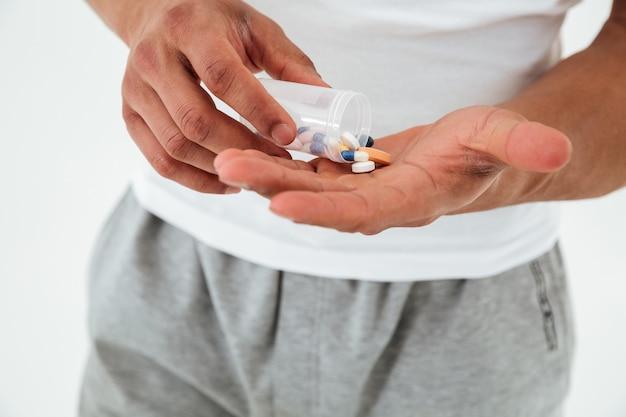 Photo recadrée de jeune sportif tenant des vitamines et des pilules pour le sport.