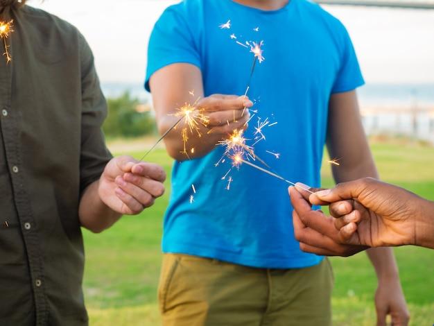Photo recadrée de jeunes atteints de feux de bengale. mains mâles tenant des étincelles. concept de célébration