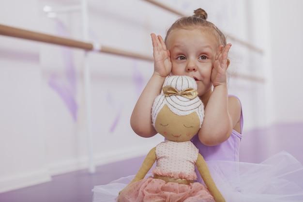 Photo recadrée d'une jolie petite fille ballerine jouant peekaboo