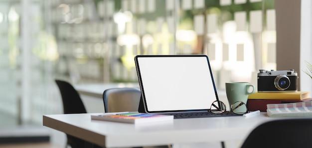 Photo recadrée d'un lieu de travail confortable avec tablette numérique et fournitures de bureau