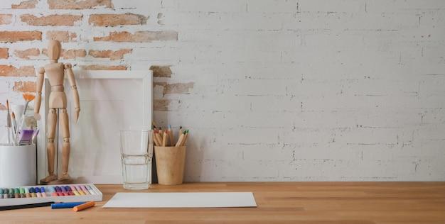 Photo recadrée d'un lieu de travail design avec des outils de peinture et des fournitures de bureau sur une table en bois et un mur de briques