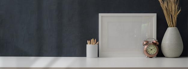 Photo recadrée d'un lieu de travail moderne avec cadre maquette et fournitures de bureau