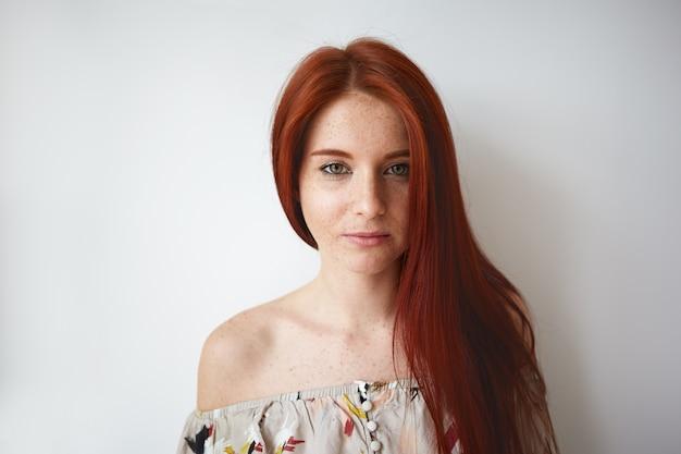 Photo recadrée de magnifique belle jeune femme de race blanche aux cheveux roux, visage taché de rousseur et épaule posant au mur de l'espace copie vierge, vêtu d'un haut floral d'été romantique. beauté, style et mode