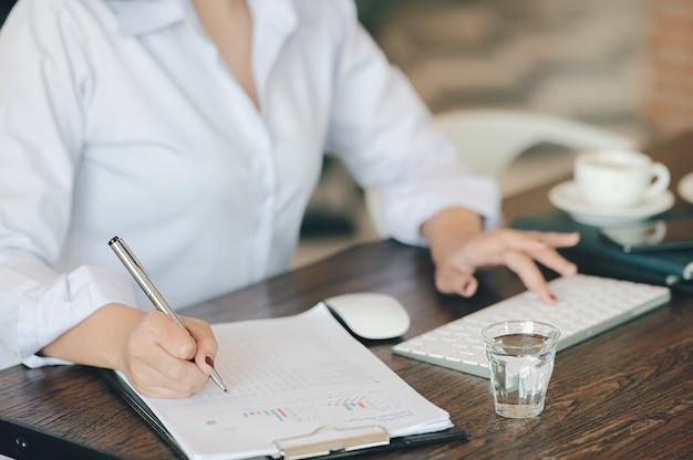 Photo recadrée de main féminine écrivant sur des documents avec un stylo tout en étant assis au bureau.