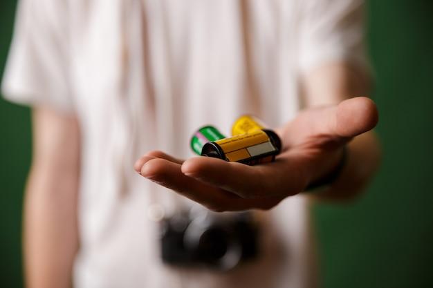 Photo recadrée de main masculine, tenant des rouleaux de caméra, mise au point sélective
