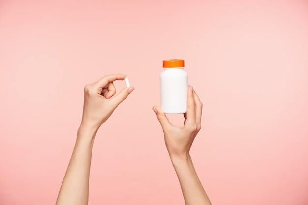 Photo recadrée des mains bien entretenues de la femelle soulevée tenant une pilule blanche et une bouteille avec couvercle orange, prenant des vitamines tout en posant sur fond rose