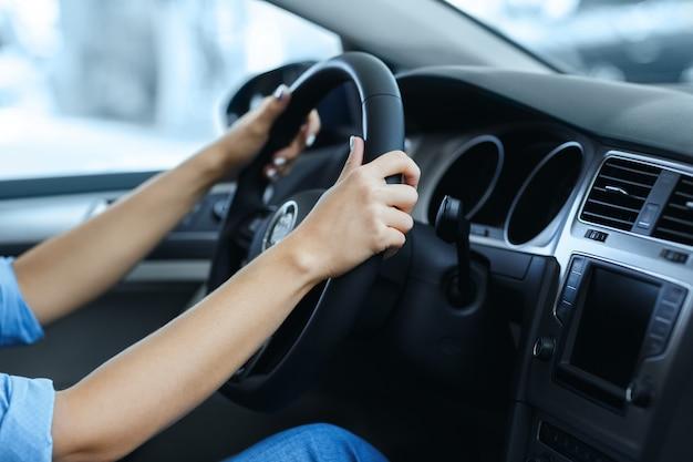 Photo recadrée des mains d'une femme sur un volant