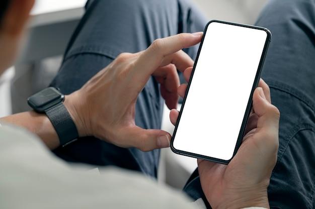 Photo recadrée de mains d'homme utilisant un smartphone avec écran vide alors qu'il était assis dans le salon à la maison.
