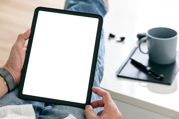 Photo recadrée de mains d'homme utilisant une tablette avec un écran vide alors qu'il était assis dans le salon à la maison.