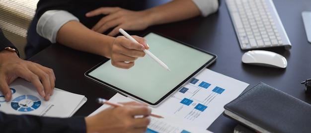 Photo recadrée de mains d'hommes d'affaires travaillant avec tablette et graphique sur la table