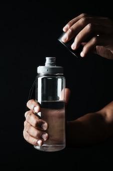 Photo recadrée de mains d'hommes afro-américains ouvrir la bouteille avec de l'eau