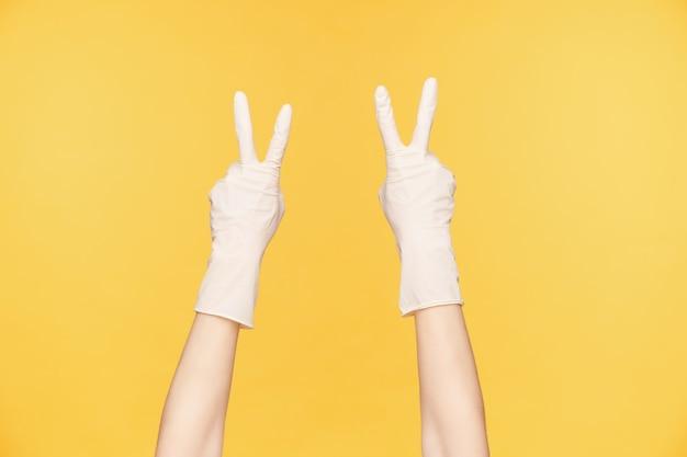 Photo recadrée de mains levées dans des gants en caoutchouc blanc formant un geste de paix avec quatre doigts, posant sur fond orange. concept de gestes et de signes de mains